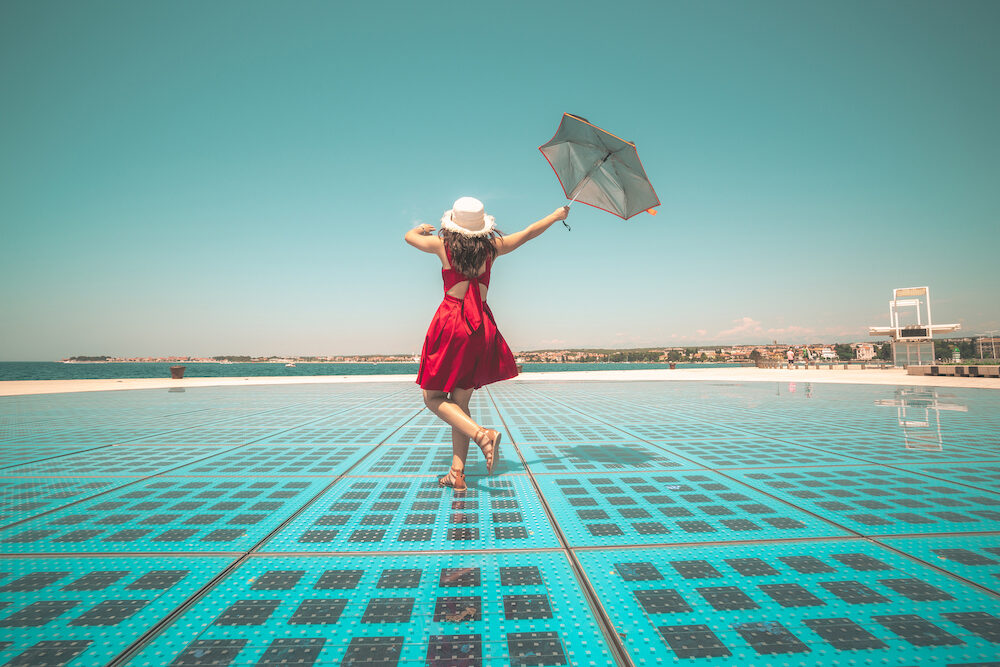 Happy woman traveler dances on outdoor disco floor in Zadar, Croatia.