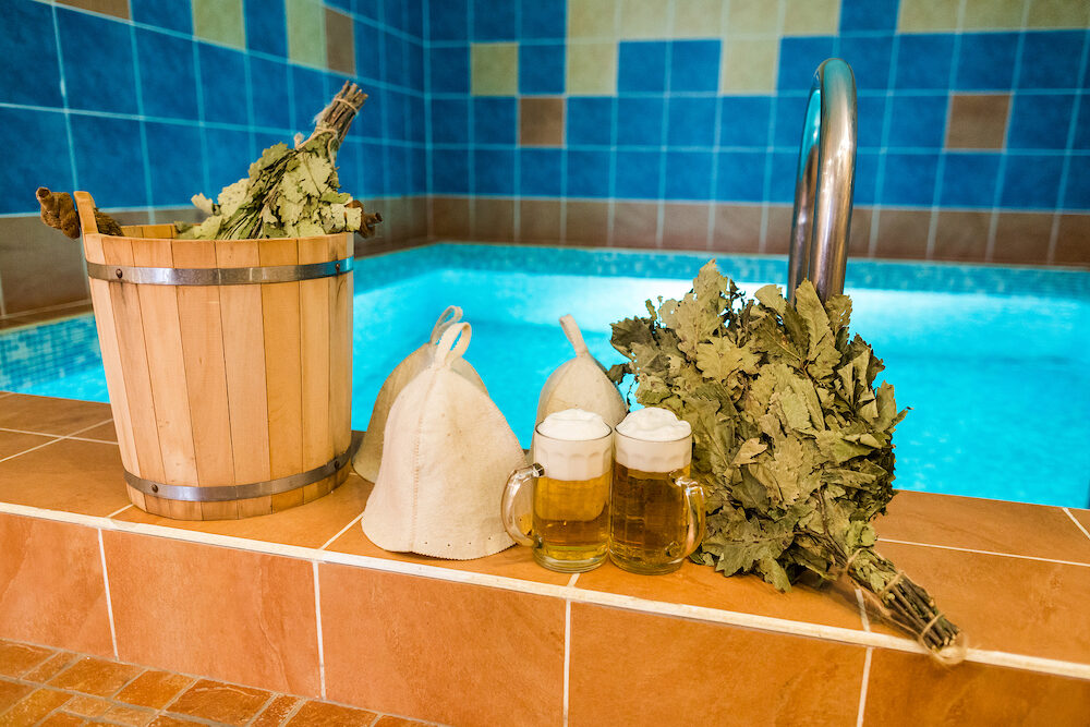 spa, rest, holidays concept. on the edge of the swimming pool with blue illumination there are few brooms made of branches of oak and linden, wool hats, bucket and three glasses of beer
