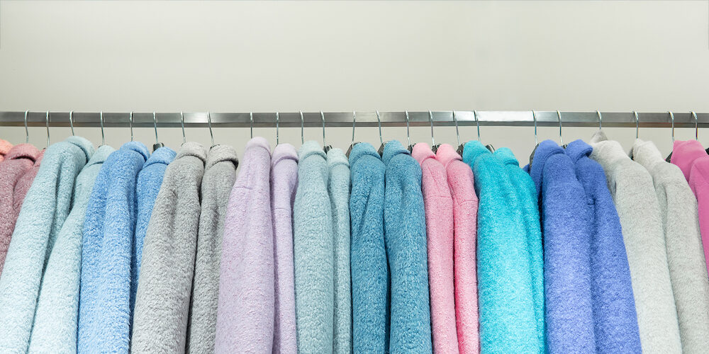 Row of colorful cotton bathrobes hanging on rack shopping. Cloth shop clothing store housecoat collection in fashion boutique