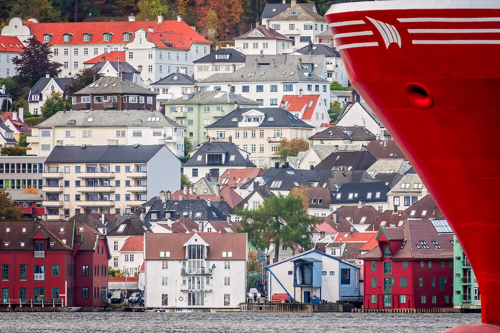 Red stern of a large ship in Bergen harbor with hillside homes in the background, Norway