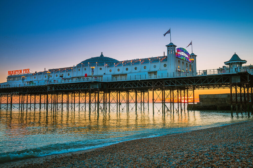 Brighton, England- Brighton Pier beach with sunset golden hour at Sussex England, UK. Brighton Marine Palace and Pier popular place for visitor.
