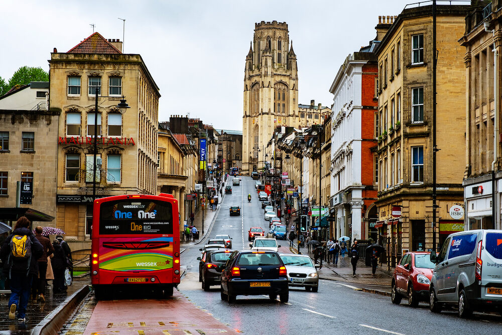 BRISTOL, UK - Famous street in the center of Bristol, UK during the rainy day. Bright cloudy sky. Various shops, cafes and restaurants. Car and bus traffic