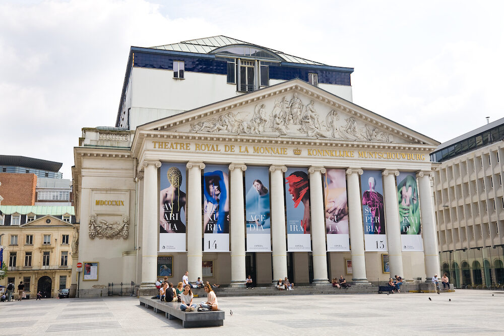 BRUSSELS, BELGIUM - : The Royal Theater of the Mint with people walking and sitting in the square in front in Brussels, Belgium