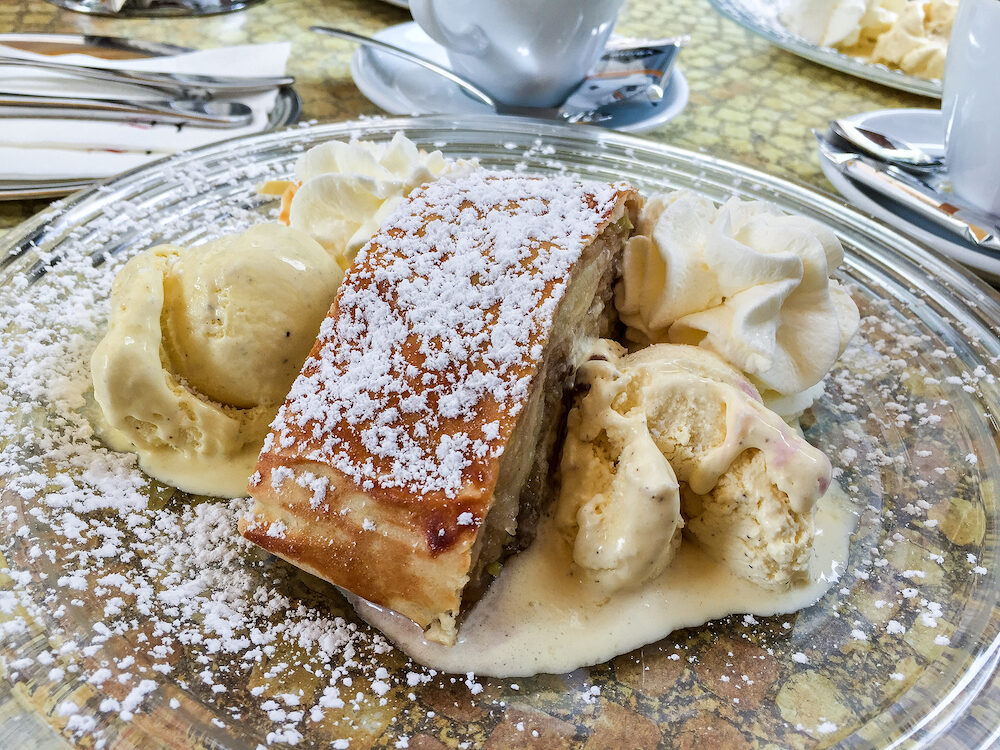 Cafe table with coffee cups and a glass plate with delicious Apfelstrudel with icecream and whipped cream outdoors in Germany in summer.