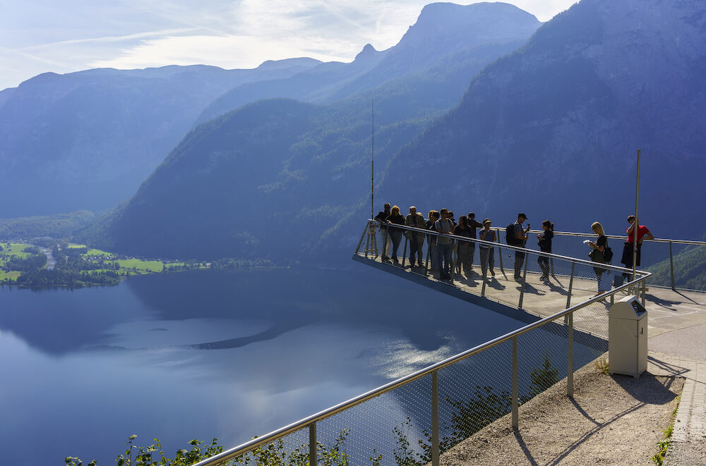 Hallstatt , Austria - Tourists visiting Skywalk platform viewing beautiful aerial view scenery of Hallstatt , small village situated on Lake Hallstatt , in the morning