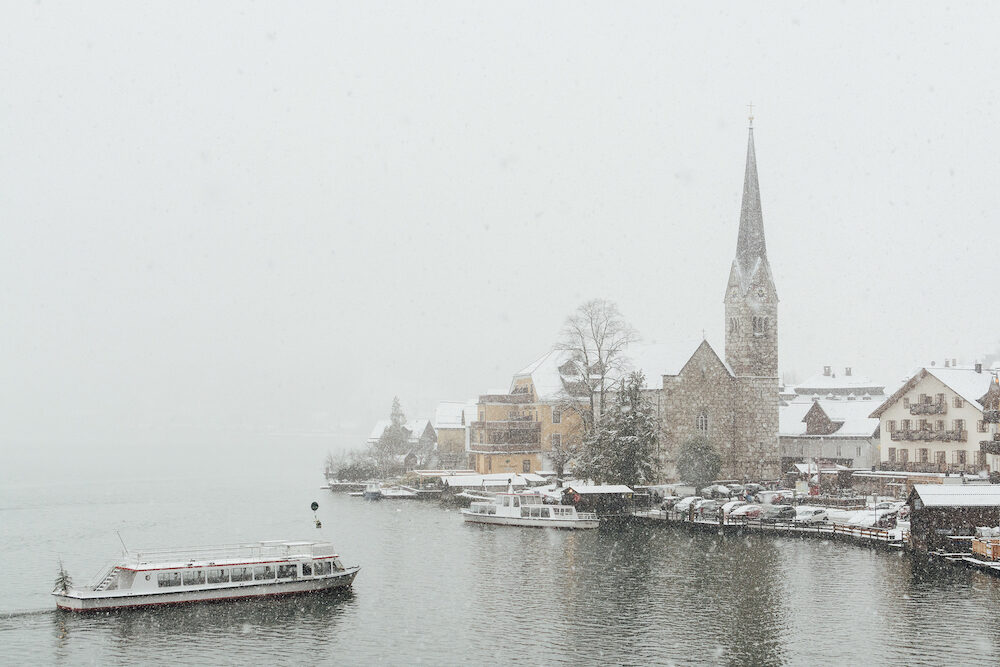 HALLSTATT, AUSTRIA - Lake ferry approaching Evangelische Pfarrkirche and old town during snow storm.