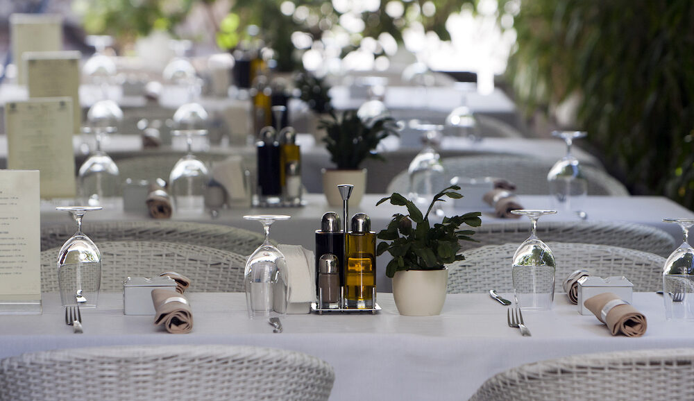 Decorated restaurant tables, white chairs and utensils.
