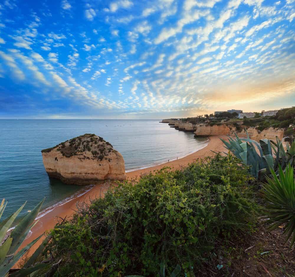 Beach Praia da Cova Redonda summer evening view. Atlantic coast seascape (Lagoa, Algarve, Portugal). People unrecognizable.