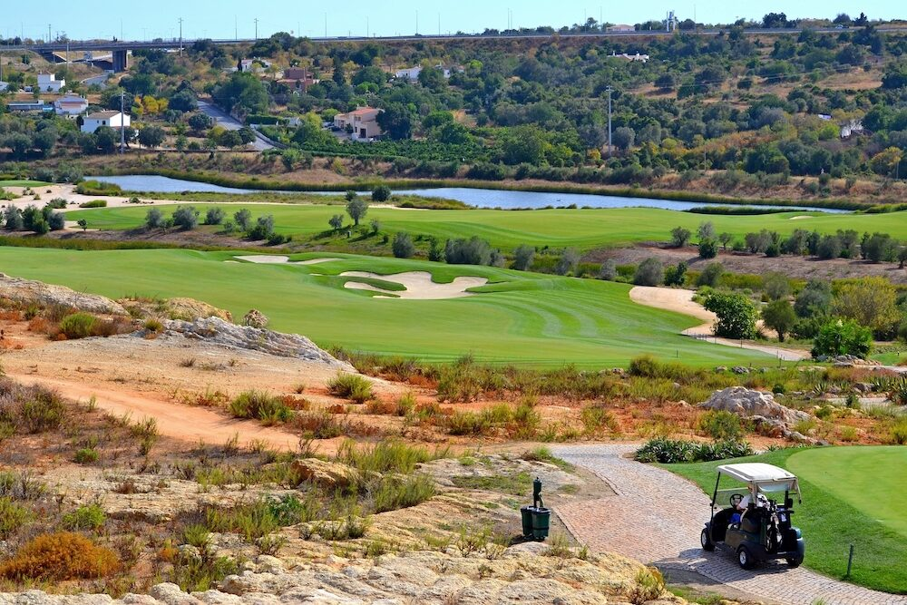 Golfer driving a golf cart to the first hole, Algarve, Portugal