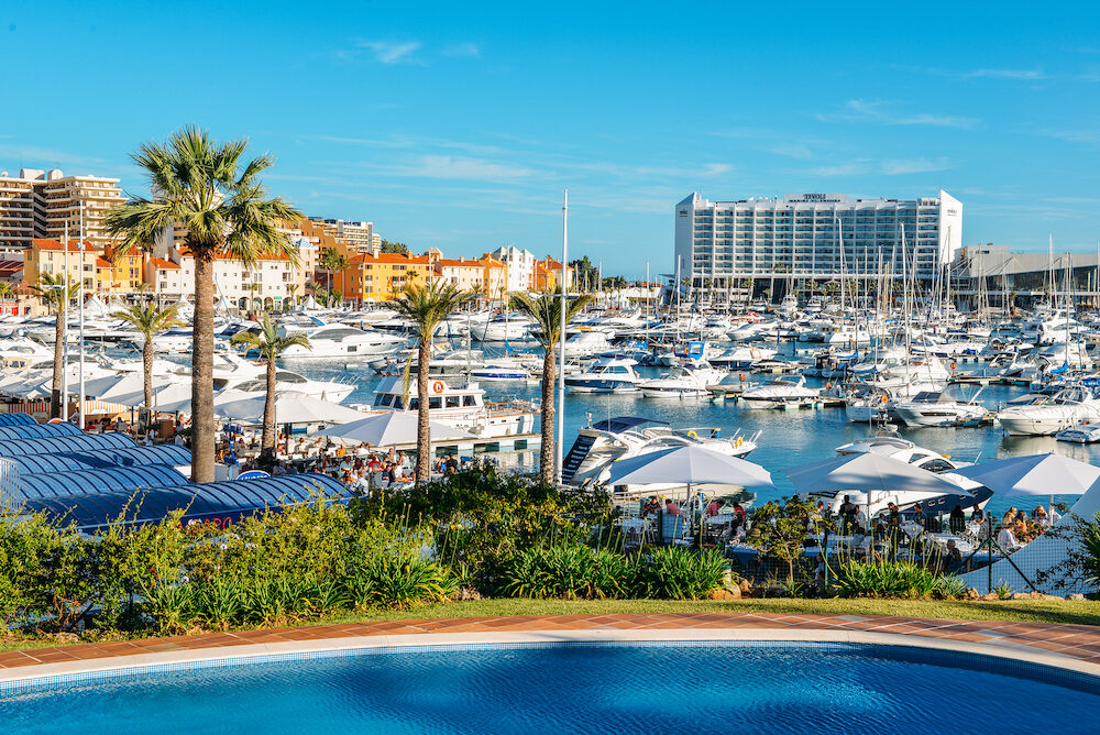 Promenade full of families next to marina at the fashionable resort town of VilaMoura in the southern Portuguese region of Algarve. Luxury Tivoli Hotel visible