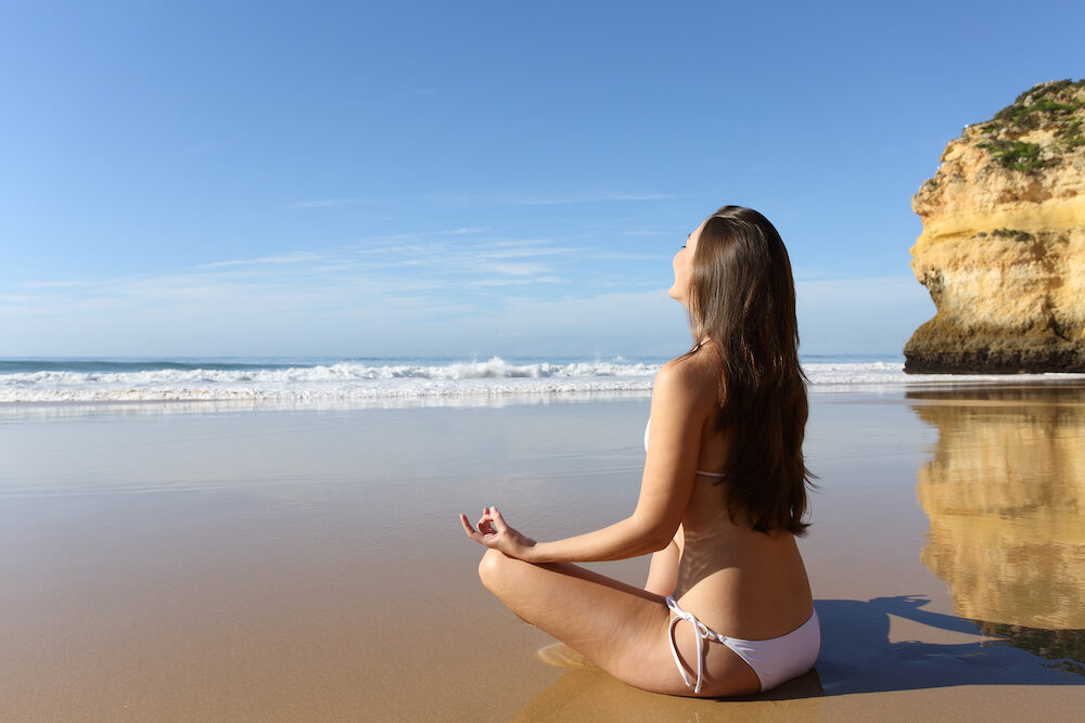 Relaxed woman in bikini practicing yoga sitting on the sand on the beach