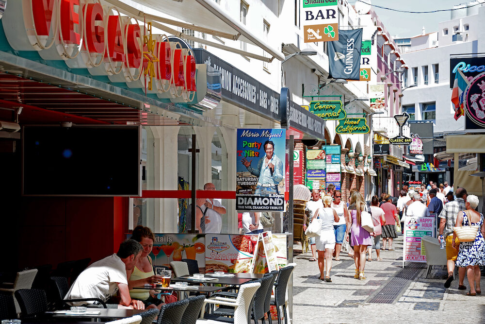 ALBUFEIRA, PORTUGAL - - Tourists relaxing at a pavement cafe in the old town with shops and shoppers to the rear, Albufeira, Algarve, Portugal, Europe,