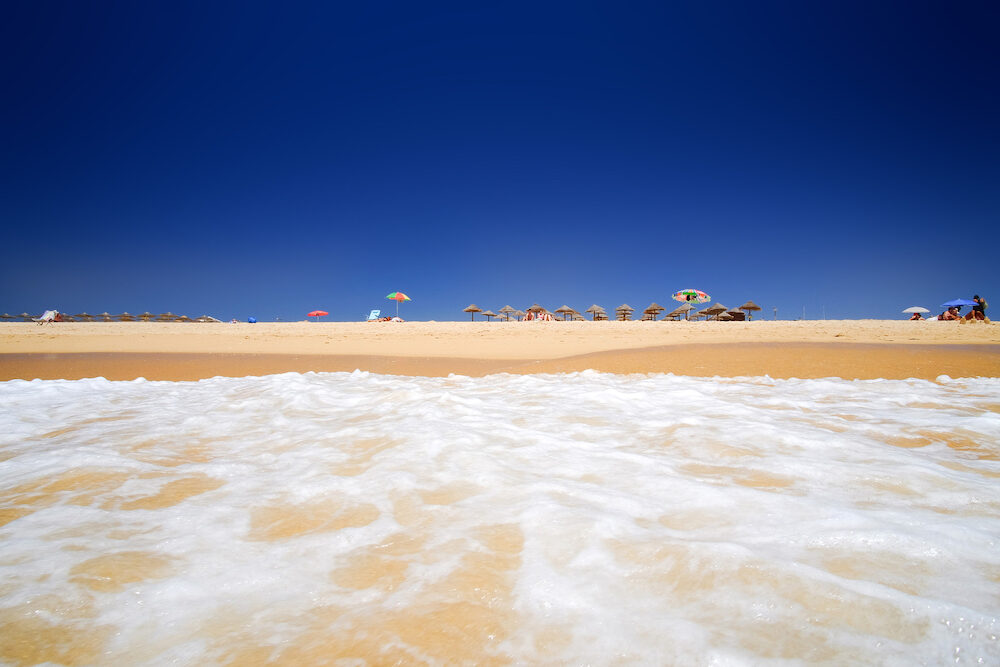ALVOR, PORTUGAL - View on the beach Alvor Poente with sun umbrellas in Algarve, Portugal.
