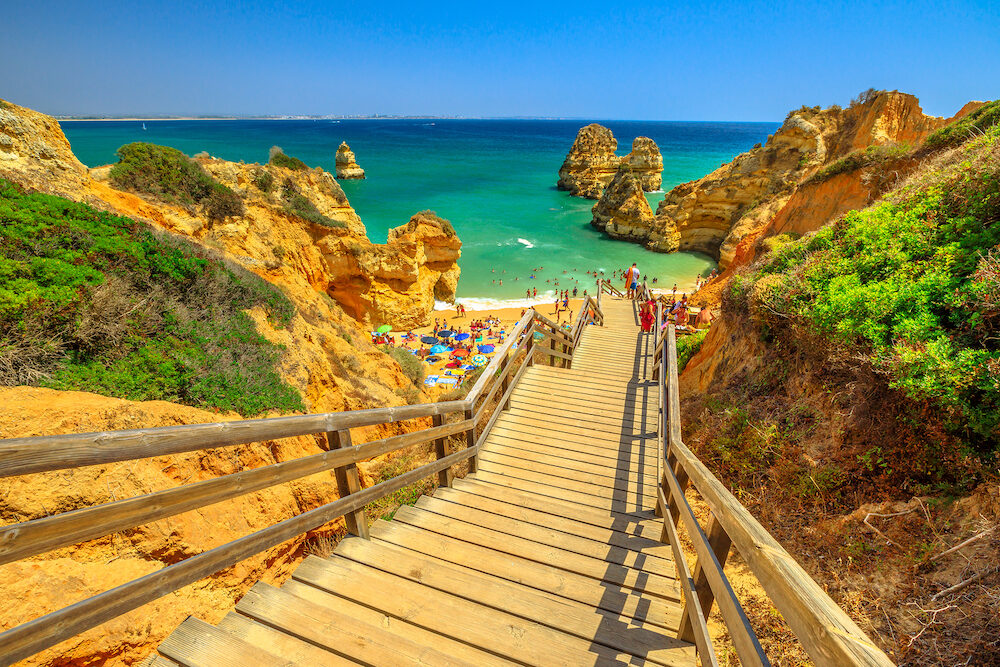 Wooden walkway to scenic Praia do Camilo in Lagos coast, Algarve, Portugal. The long stairs to clear waters of Algarve. Summer holidays in Europe.