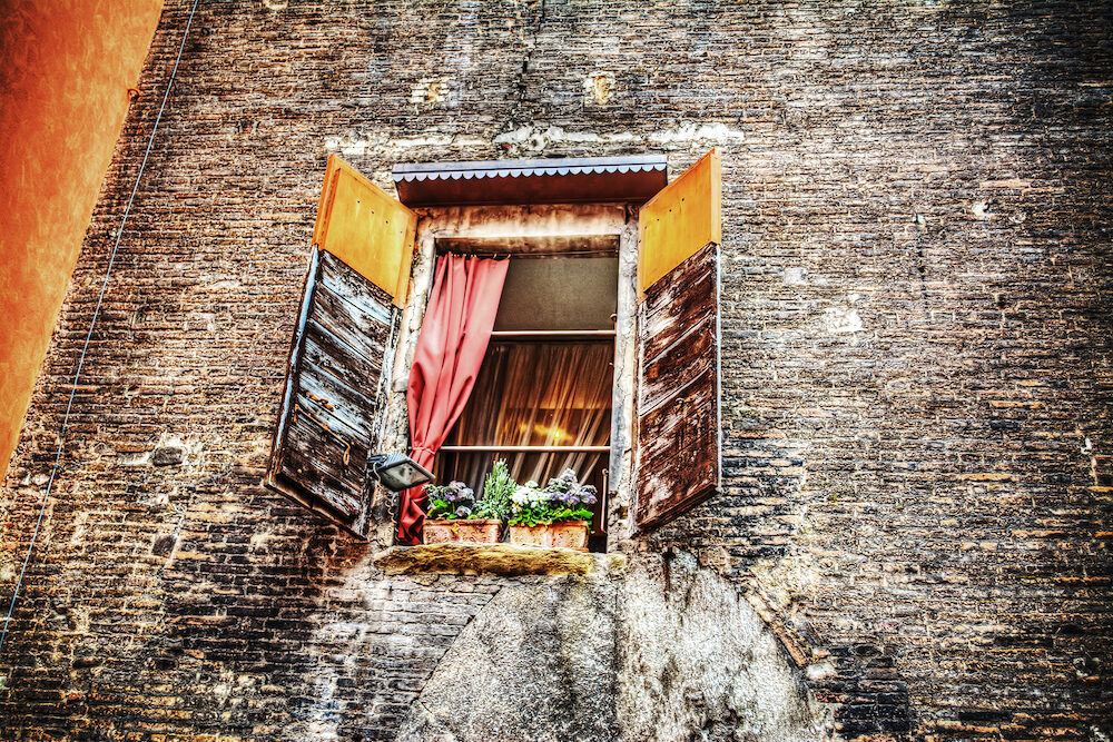 rustic window in a brick wall in Bologna Italy