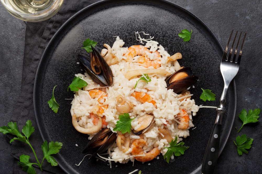 Delicious seafood risotto with shrimps, prawns, mussels. Dressed with parmesan cheese and parsley. Top view with white wine glass