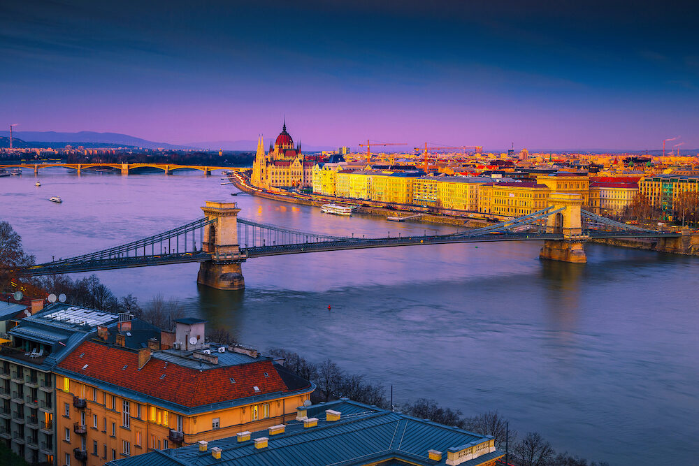 Famous European touristic travel location. Amazing cityscape panorama with spectacular Chain bridge and Parliament building at colorful sunset, Budapest, Hungary, Europe
