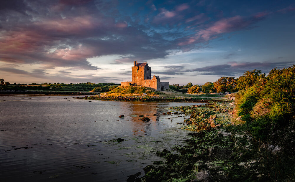 GALWAY, IRELAND - Dunguaire Castle on the bank of ocean bay during sunset. Kinvara, Co. Galway, Ireland