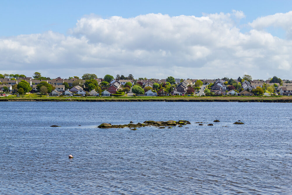 Lough Atalia bay with houses in background and cloud reflection, Galway, Ireland