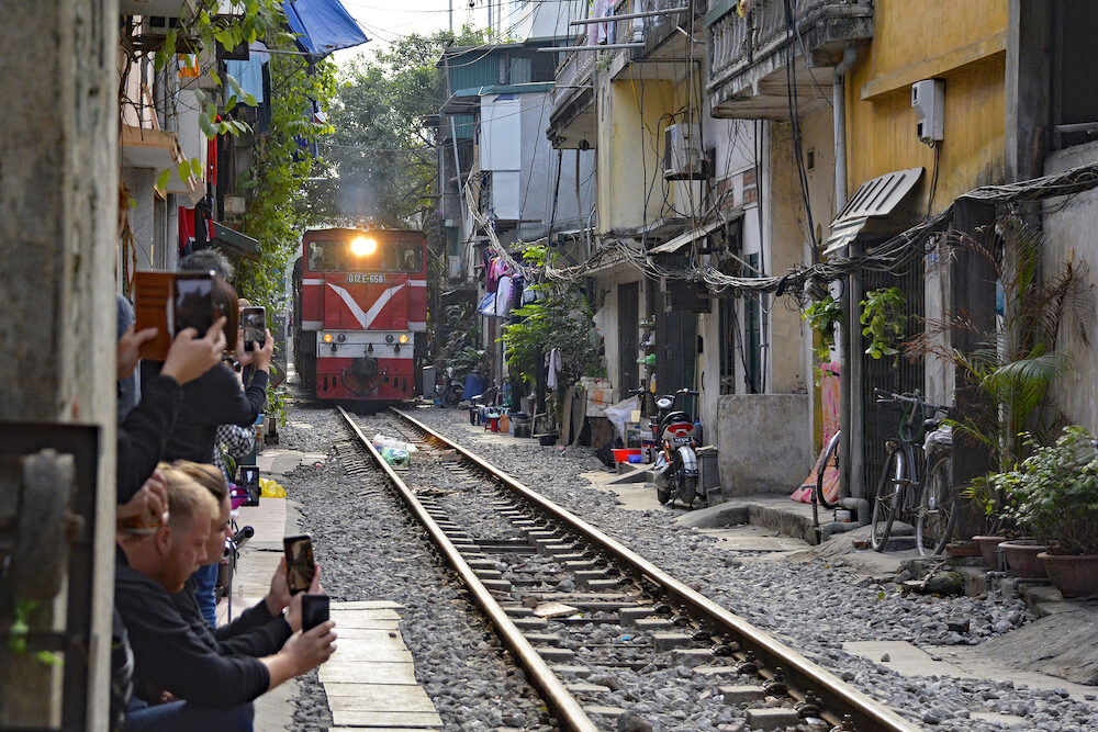 Hanoi, Vietnam - Tourists take photographs of the 15.30 train from Hanoi to Sapa as it goes along a residential street in central Hanoi which has grown up around the north-bound train track. The street is often referred to as train str