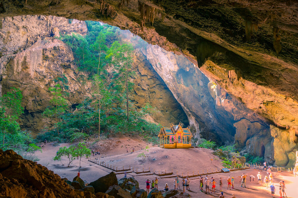 Buddhist temple in the cave with unidentifiable tourists around. Khuha Kharuehat Pavilion in Phraya Nakhon Cave in Kui Buri, Thailand