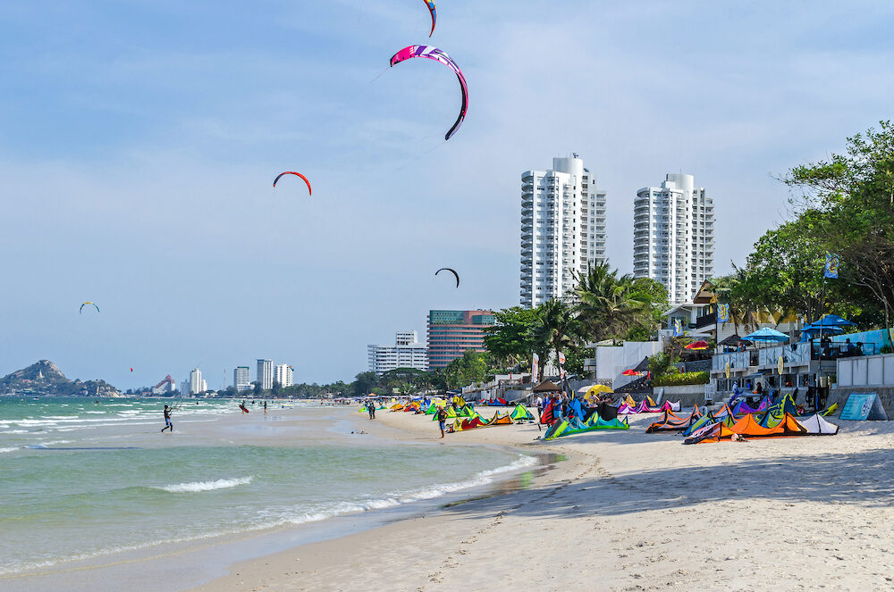 Hua hin, Thailand - View at Hua hin town, a coastal city near Bangkok on the Gulf of Thailand, and its beach front with kites flying, hotel buildings and the Chopsticks Hill Khao Takiap, known locally as Monkey Mountain to the left