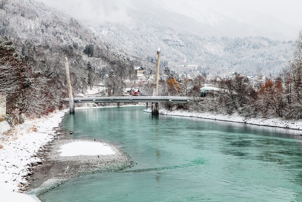 Beautiful Innsbruck with river Inn on snow winter day. Magic color of water.