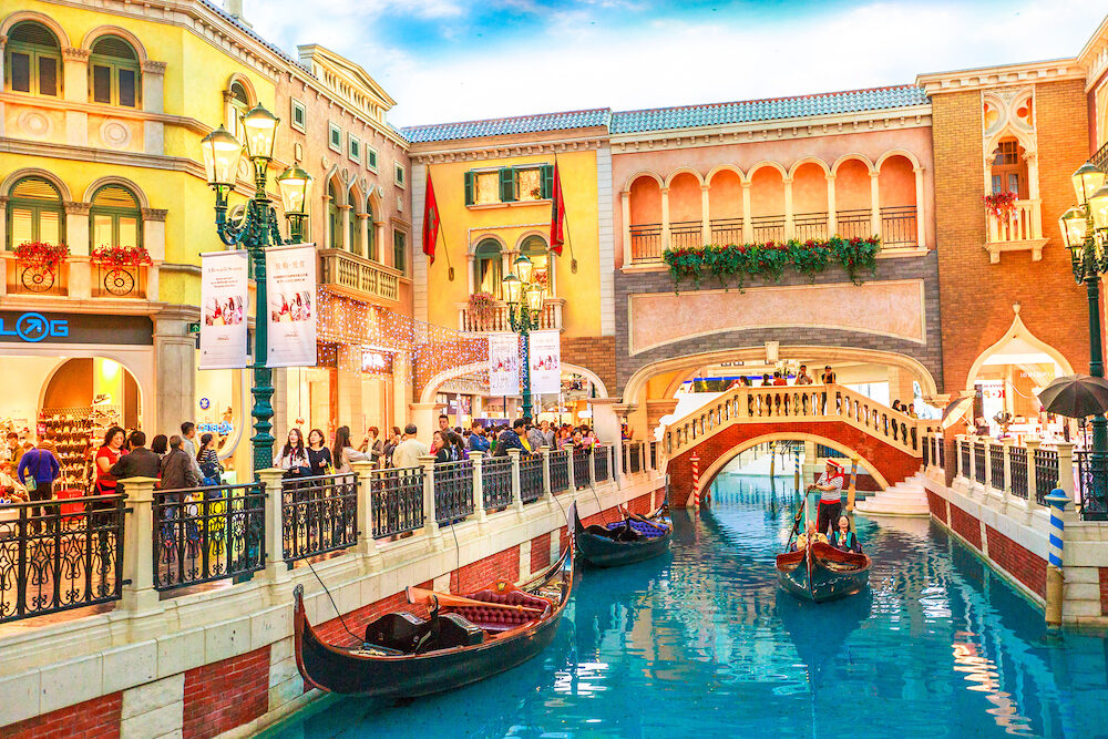 Macau, China - : Canals with Venetian bridge of the Venetian style Casino. Inside luxury shopping mall in the Venetian Hotel in Cotai Strip.