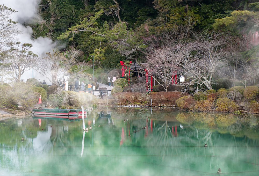 """Hot spring water (Hells), the """"sea hell"""" features a pond of boiling and red torii gateway in Umi Jigoku at Beppu, Oita-shi, Kyushu, Japan"""