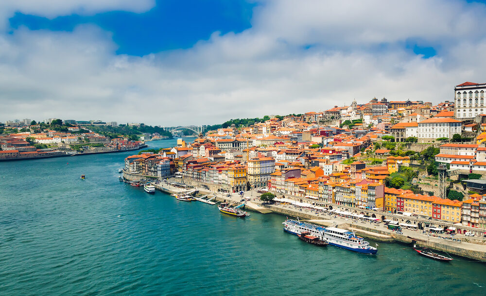 Porto, Portugal: view over Porto old town with colorful buildings and red roofs. Promenadein Cais de Ribeira along Duoro river on a sunny day.