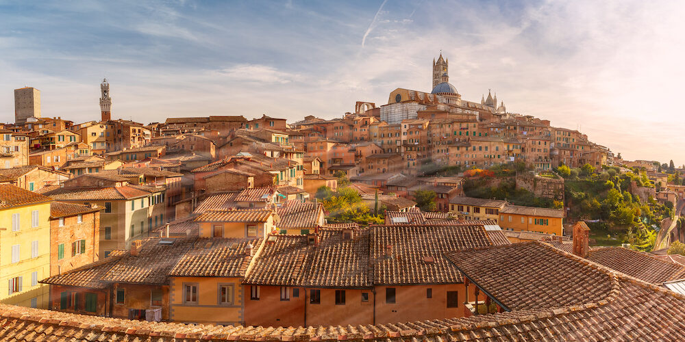 Beautiful panoramic view of Old Town with Dome and campanile of Siena Cathedral, Duomo di Siena, and Mangia Tower or Torre del Mangia at sunset, Siena, Tuscany, Italy