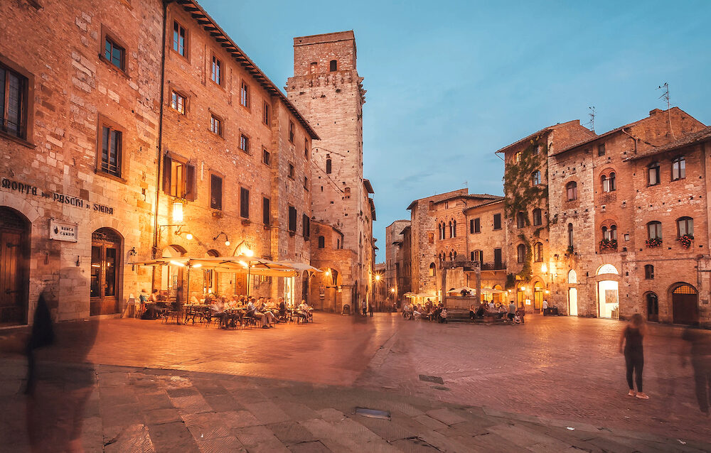 SAN GIMINIANO, ITALY - Shadows from moving tourists at evening in beautiful ancient town of Tuscany on 19 September 2018. Historic Centre of San Gimignano is a UNESCO World Heritage Site