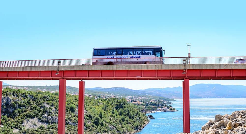 ZADAR, CROATIA - Bus rides over the bridge located above the sea bay on a summer day, near Zadar, Croatia.
