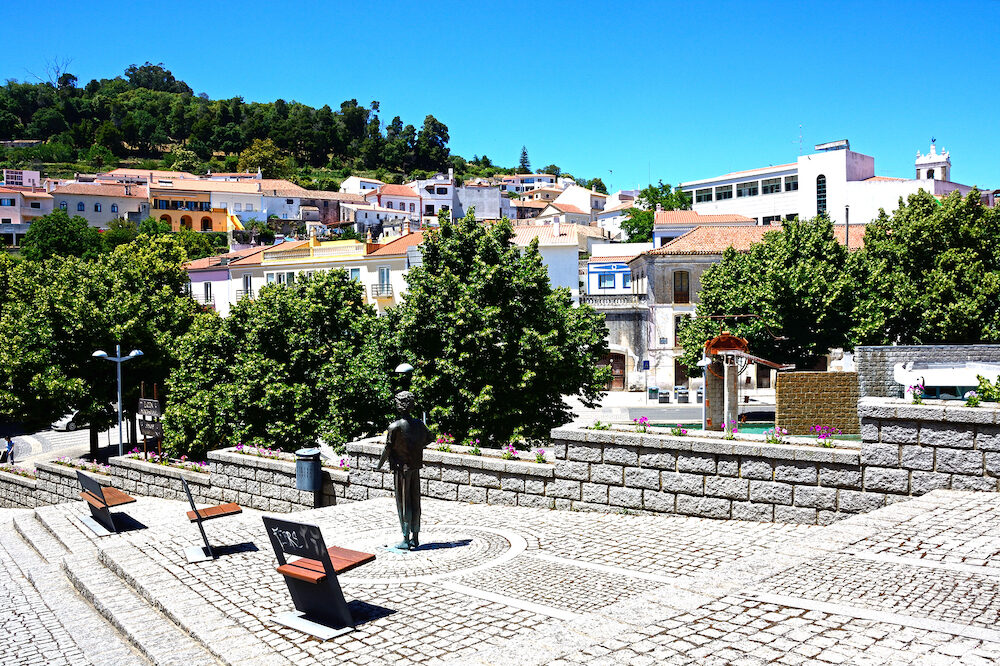 MONCHIQUE, PORTUGAL - - View of the town buildings with a modern art statue in the foreground and a boy standing in the park, Monchique, Algarve, Portugal, Europe