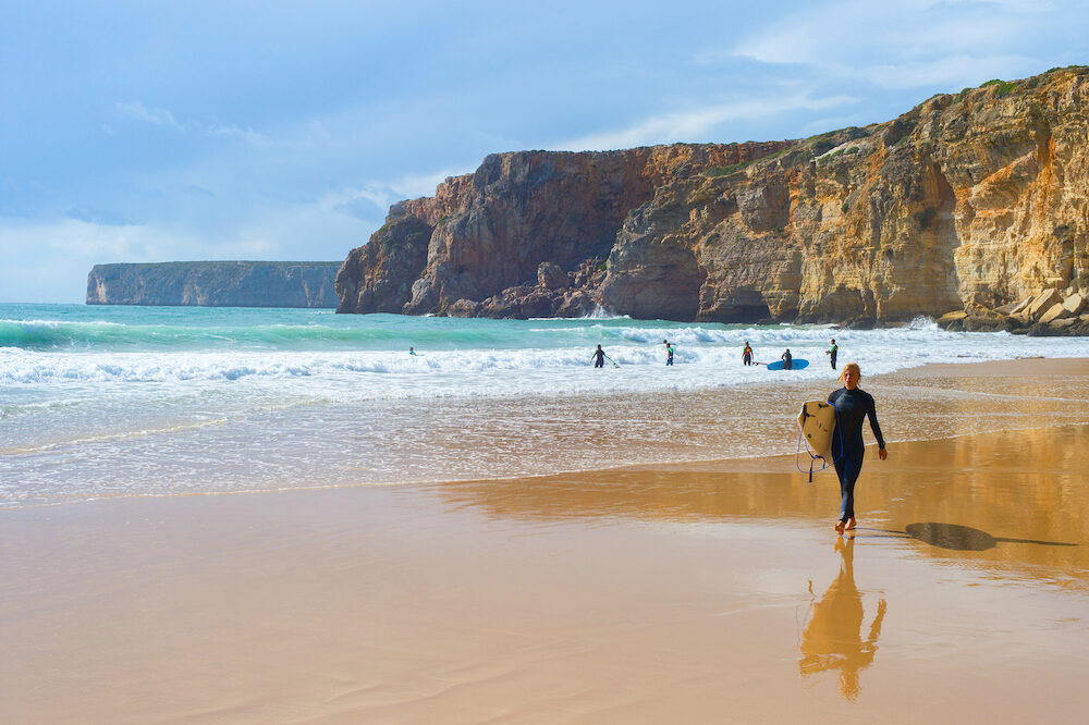 SAGRES, PORTUGAL - Young man walking by sandy beach with surfboard. ALgarve is a famous surfing destination in Portugal