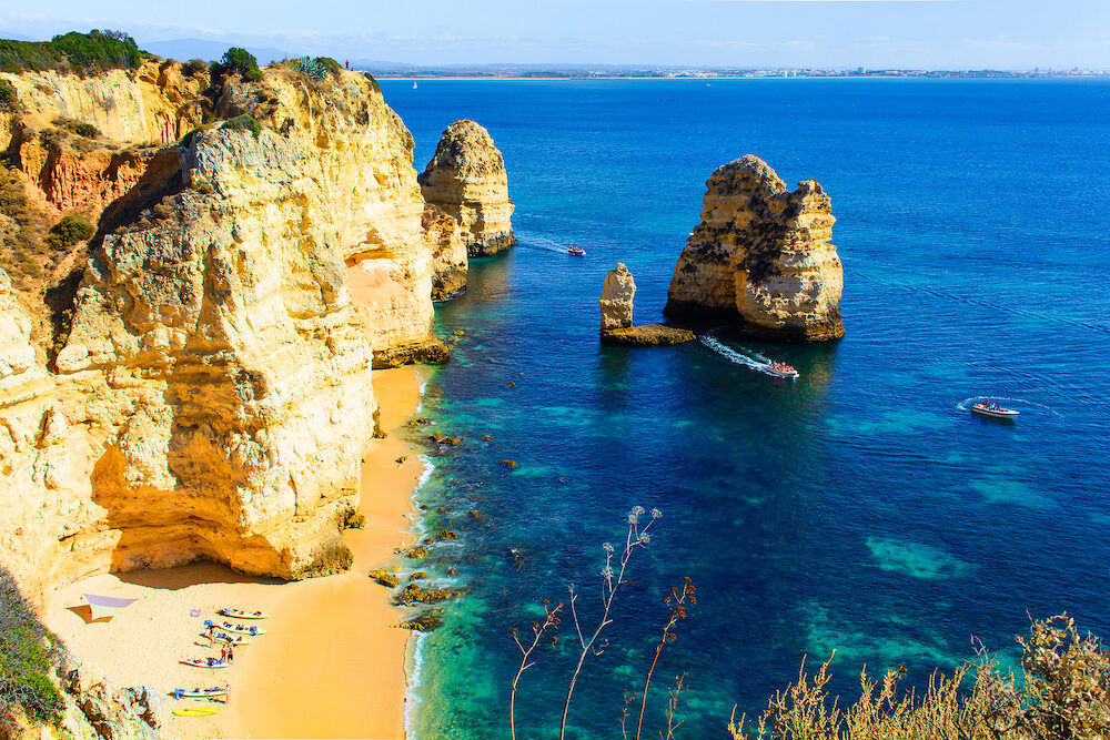 beautiful hidden sandy beach between rocks and cliffs with kayaks and turquoise sea at Ponta da Piedade. Algarve region. Portugal