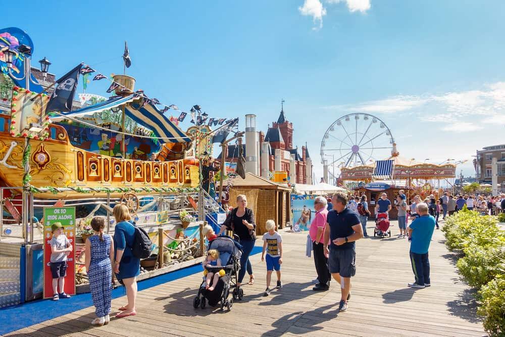 Cardiff United Kingdom - : People enjoying themselves on a sunny day at the Cardiff Bay Beach Fair an urban seaside beach fair at Roald Dahl Plass in Cardiff Bay Cardiff.