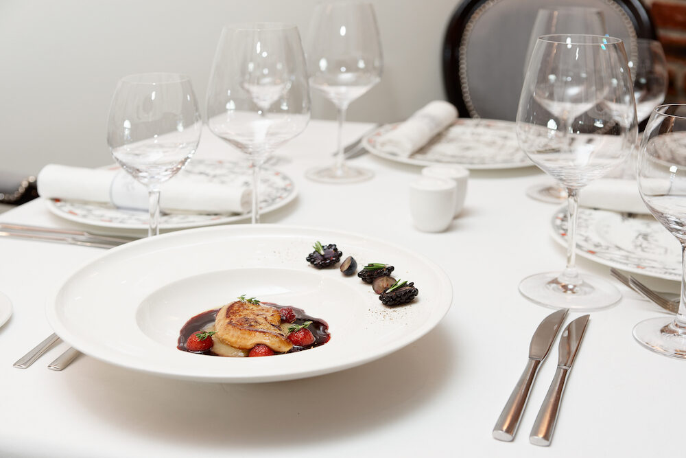 Foie gras dish with red porto sauce and berries, formal restaurant setting