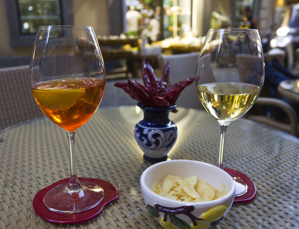 AMALFI, ITALY - Happy hour in Amalfi. Two glass one with a spritz and the other with white wine with the traditional Amalfi ceramics and red hot chilli pepper