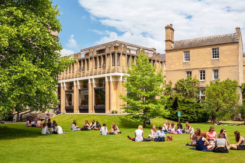 OXFORD ENGLAND - Students relaxing on the grass outside Balliol College of Oxford University