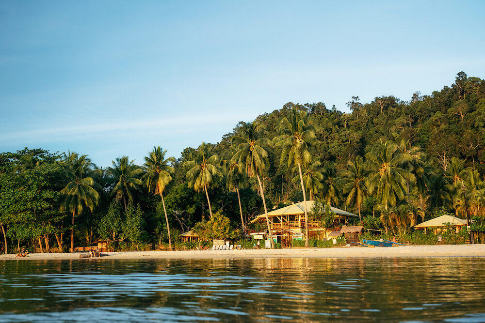 Port Barton, Palawan, Philippines - People on tropical beach with trees against wooden hotel at sunset