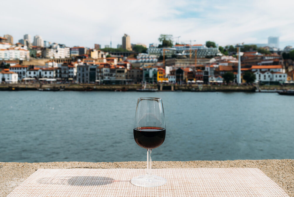 Glass of red Port wine overlooking Vila Nova de Gaia, Porto, Portugal