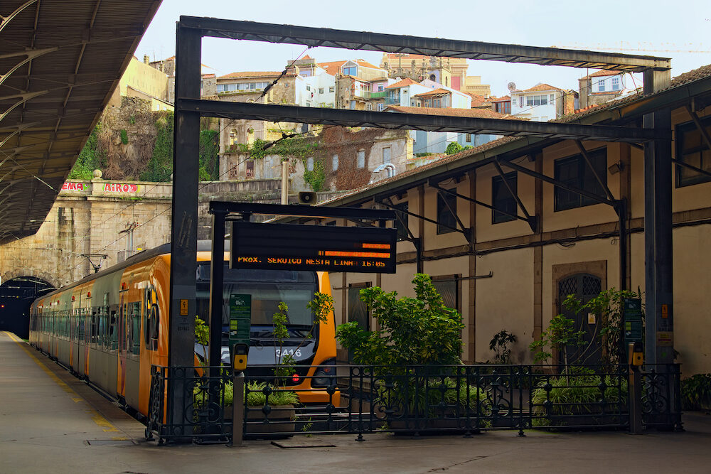Porto, Portugal - Landscape view of Porto old railway station Sao Bento with typical yellow train near the platform. Vintage residential houses on a hill in the background