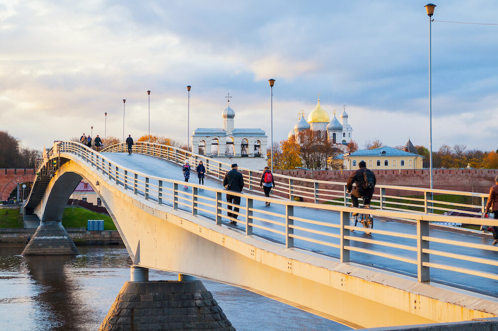 VELIKY NOVGOROD, RUSSIA - St Sophia Cathedral and people walking on the footbridge in Veliky Novgorod in autumn evening