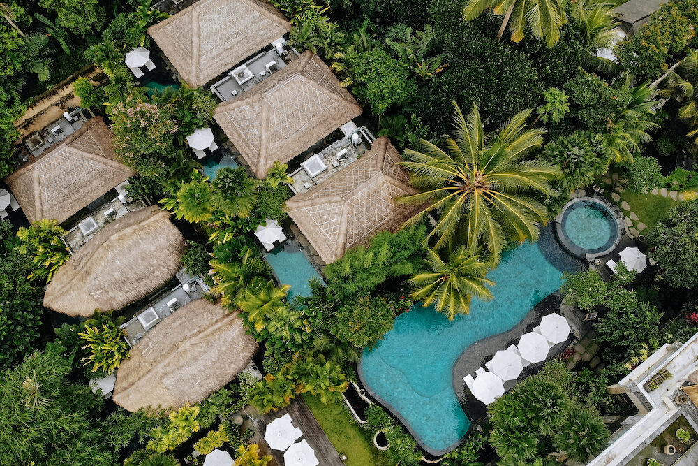 Aerial view of luxury hotel with straw roof villas and pools in tropical jungle and palm trees. Luxurious villa, pavilion in forest, Ubud, Bali