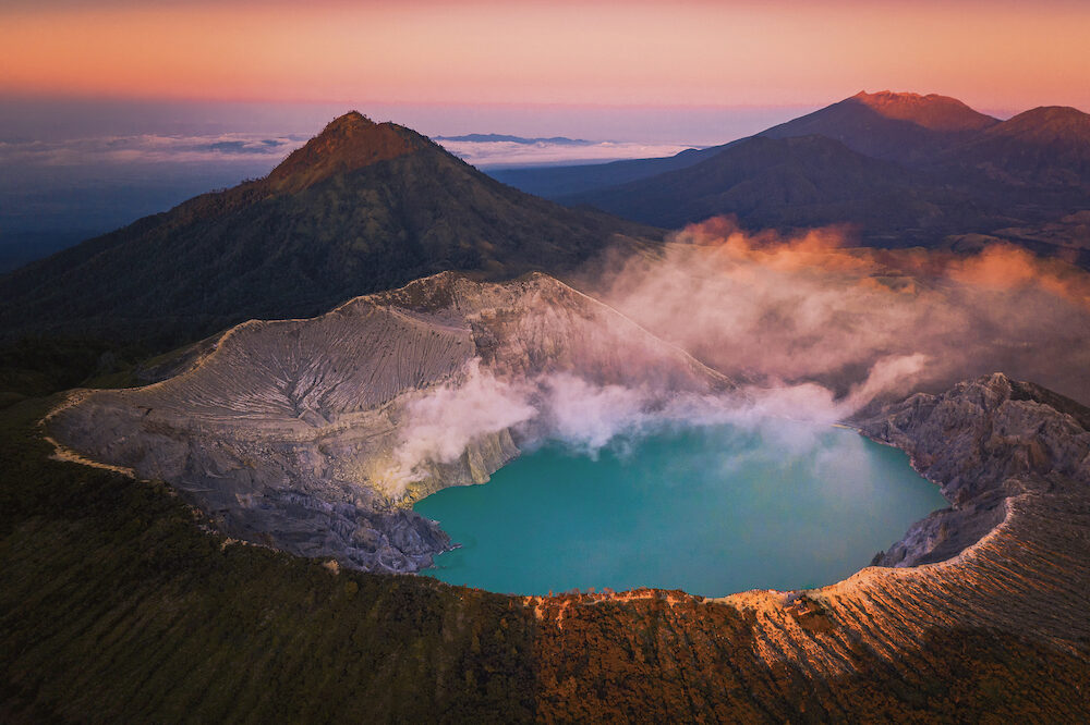 Aerivl view of Kawah Ijen volcano with turquoise sulfur water lake at sunrise. Panoramic view at East Java, Indonesia. Natural landscape background.