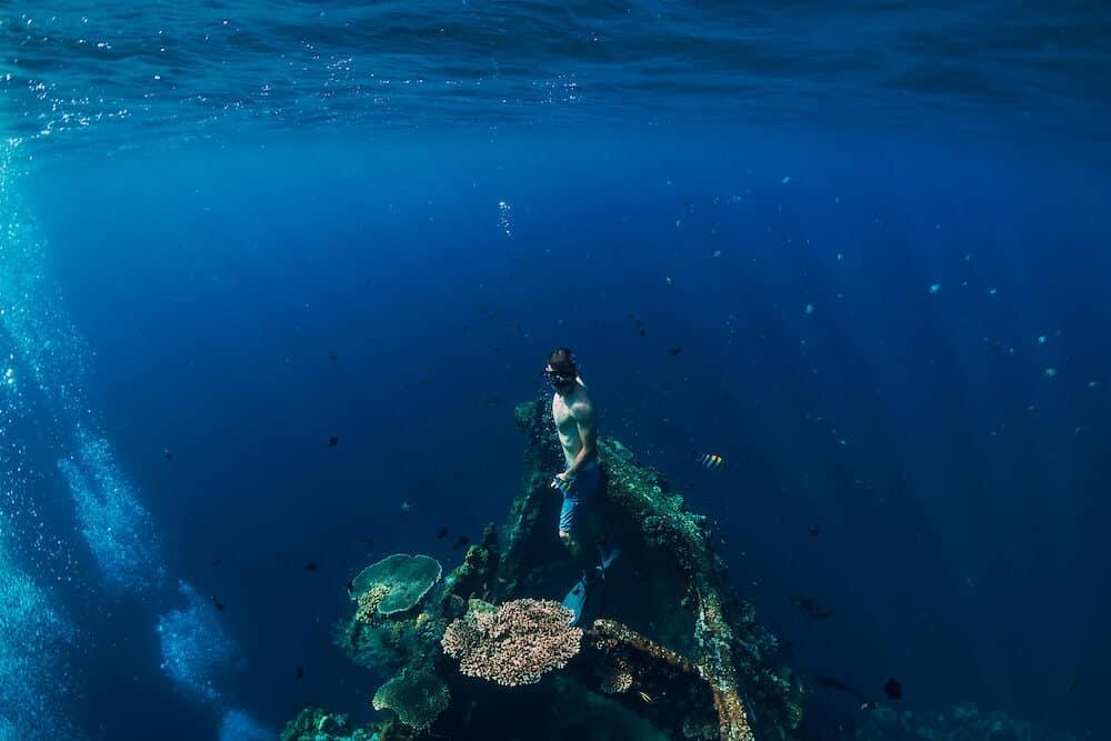Freediver man dive underwater at shipwreck in Bali. Freediving in ocean