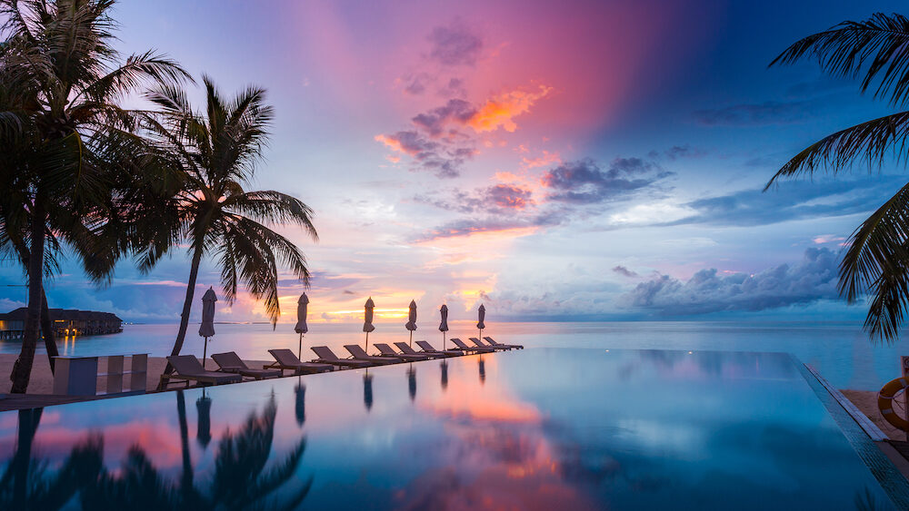 Luxury infinity pool overlooking sunset sea and sky reflection. Amazing swimming pool and beach background
