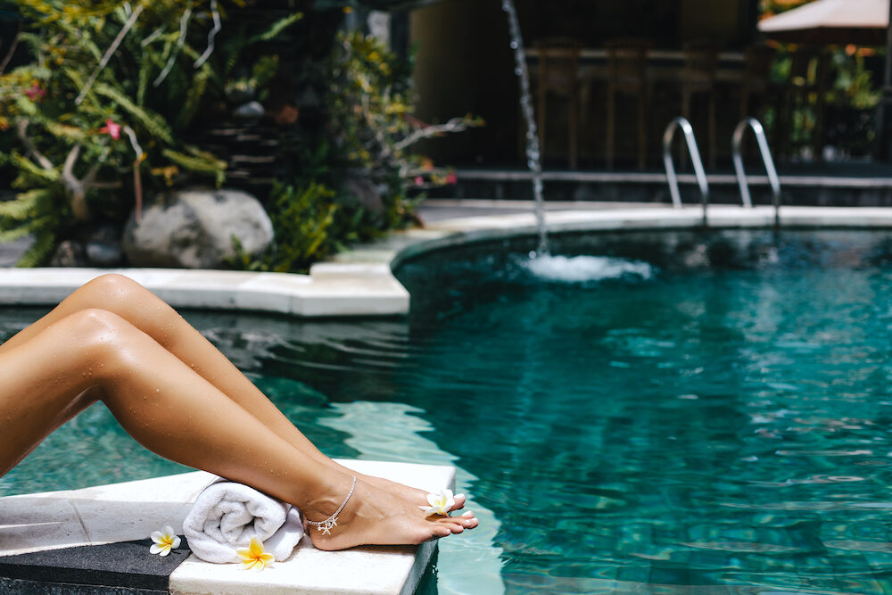 Woman relaxing in swimming pool in Bali luxury resort. Foot spa and skin care lifestyle photo.