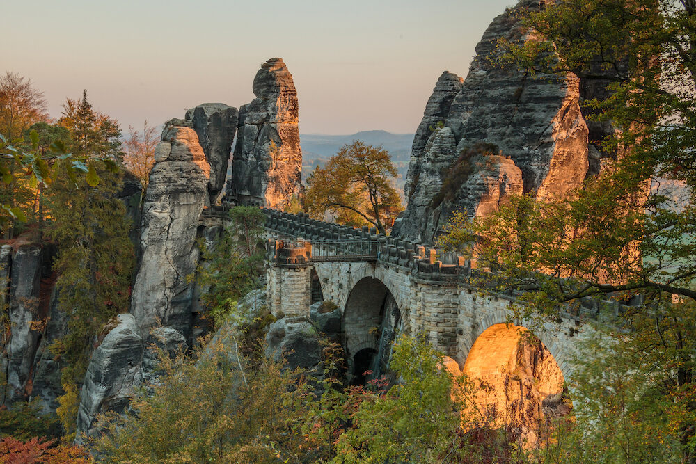 Bastei bridge in the evening sun in the national park Saxon Switzerland. Elbe sandstone mountains with trees in autumn colors and rock formations